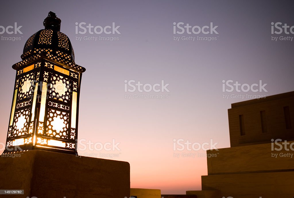 An Arabian sunset with an ornate lantern in the foreground stock photo