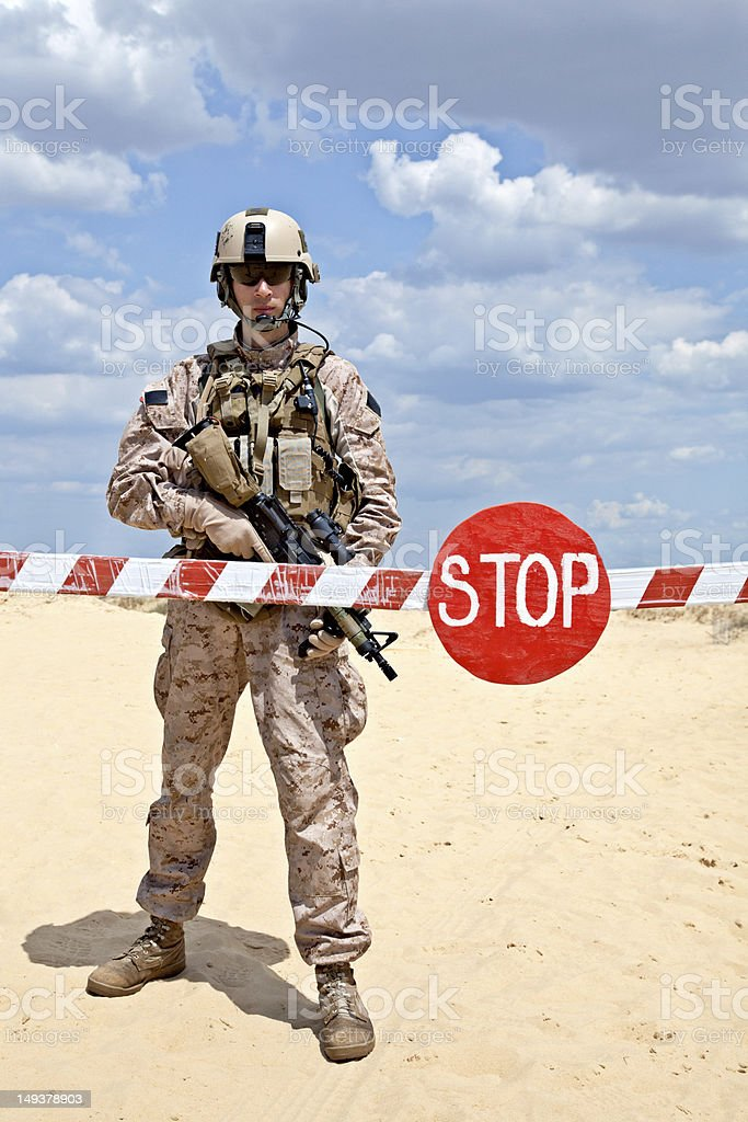 An armed soldier guarding behind a Stop barrier stock photo