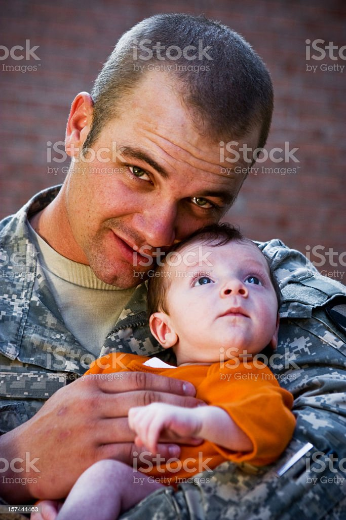 An army father holding his baby royalty-free stock photo