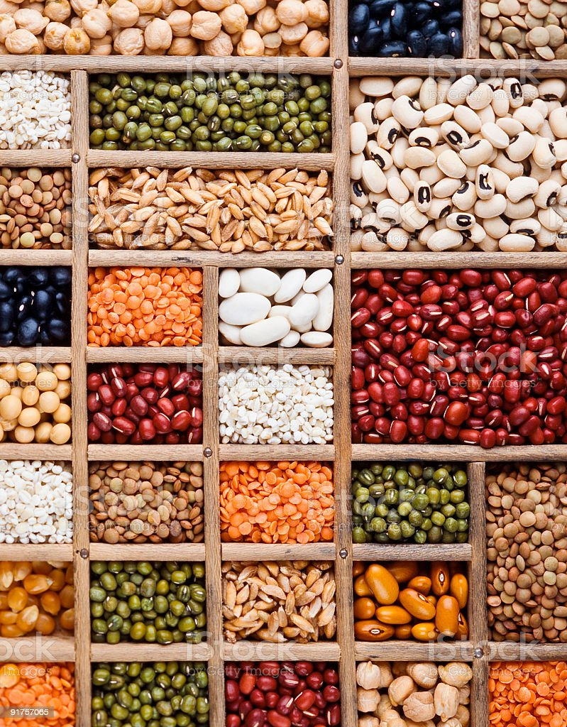 An arrangement of grain, seeds and legumes on a wooden box stock photo