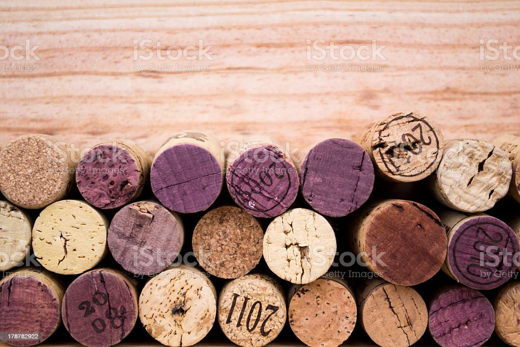 An array of wine corks on a wooden surface stock photo