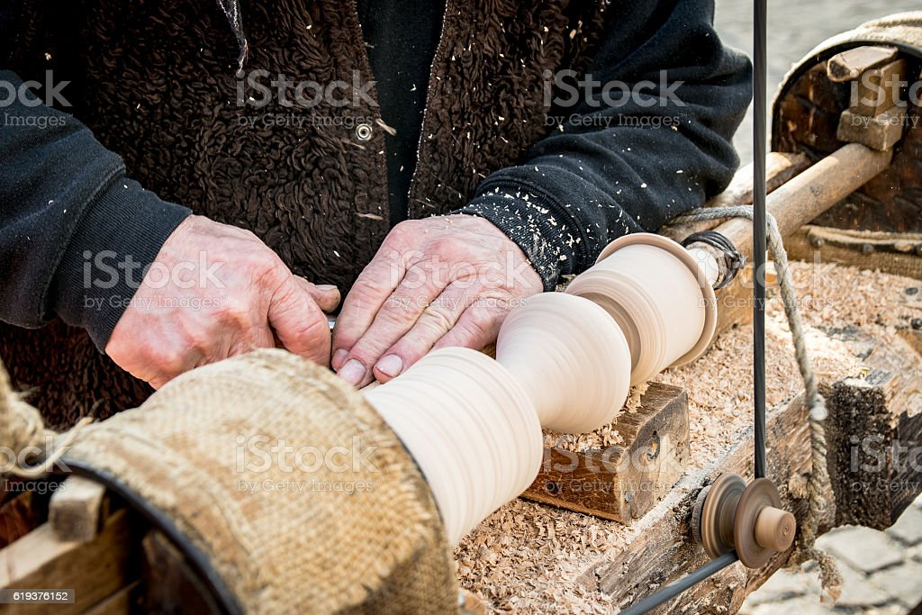 An artisan carves a piece of wood using a lathe. stock photo