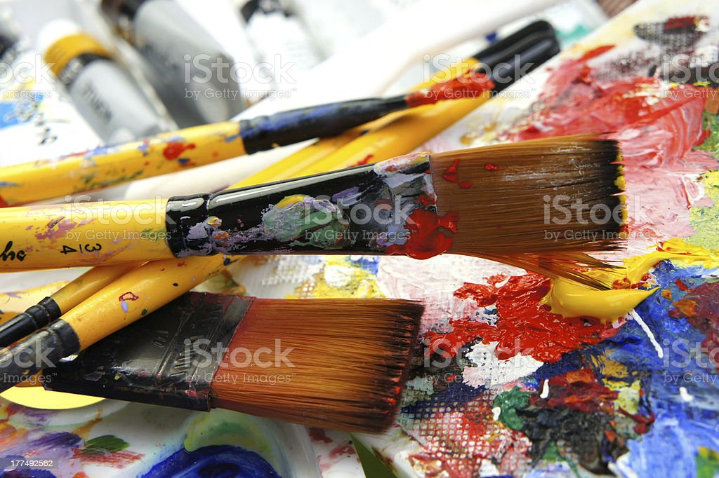 An artist palette with brushes filled with various paints stock photo