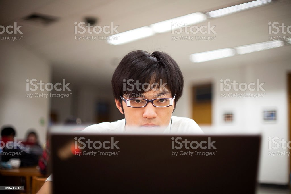 An Asian male student with glasses using a laptop royalty-free stock photo
