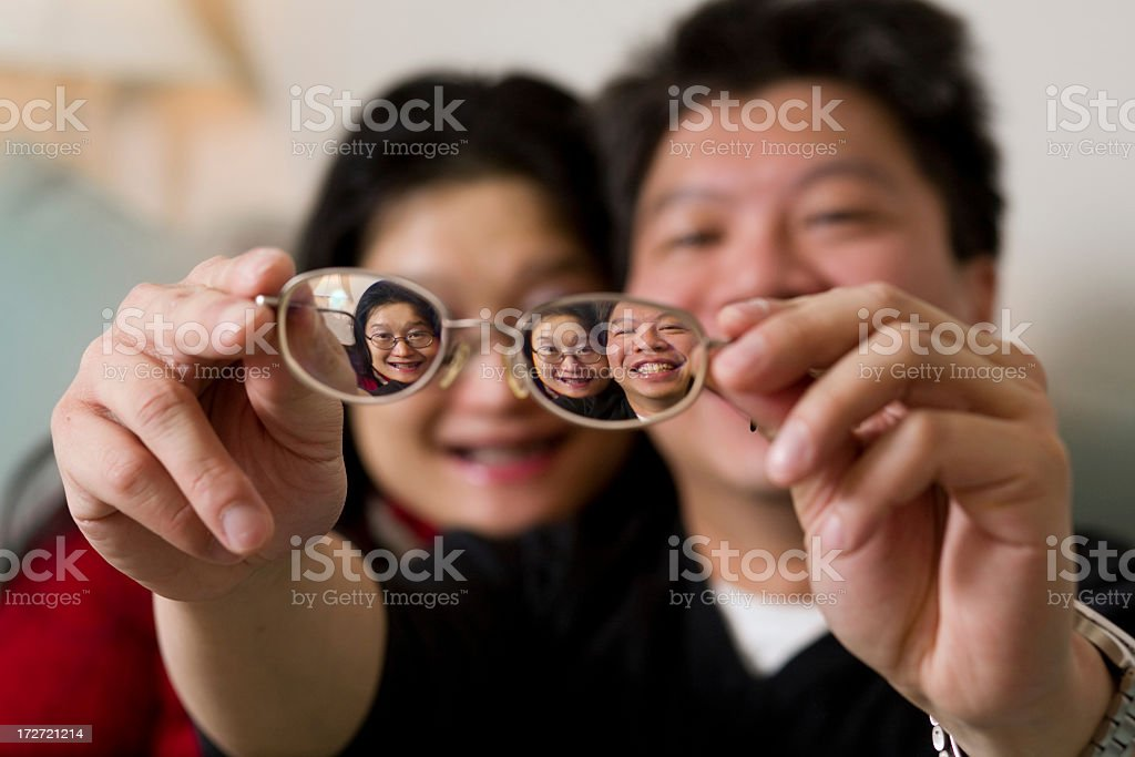 An Asian man and woman holding up glasses royalty-free stock photo