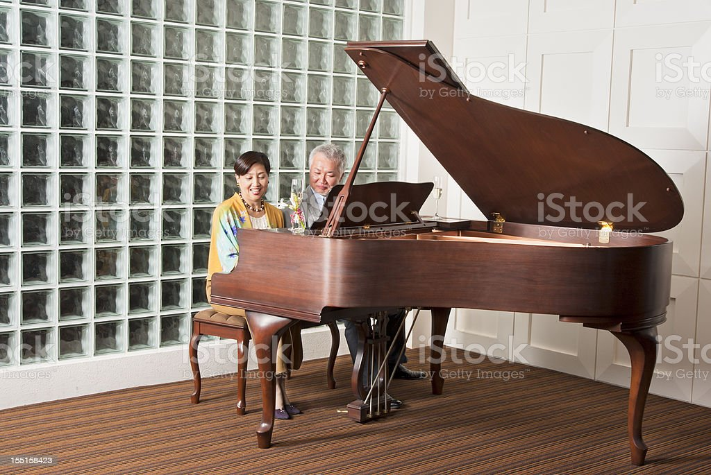 An Asian senior couple playing the grand piano stock photo