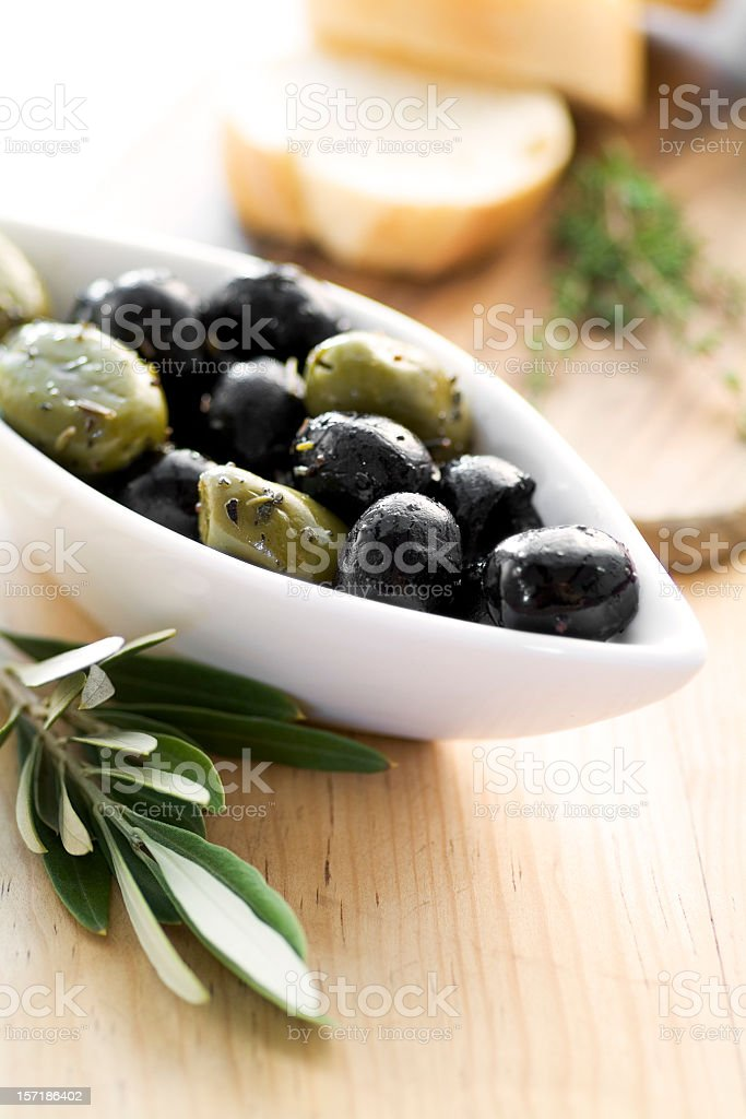 An assortment of olives in a bowl on a table royalty-free stock photo