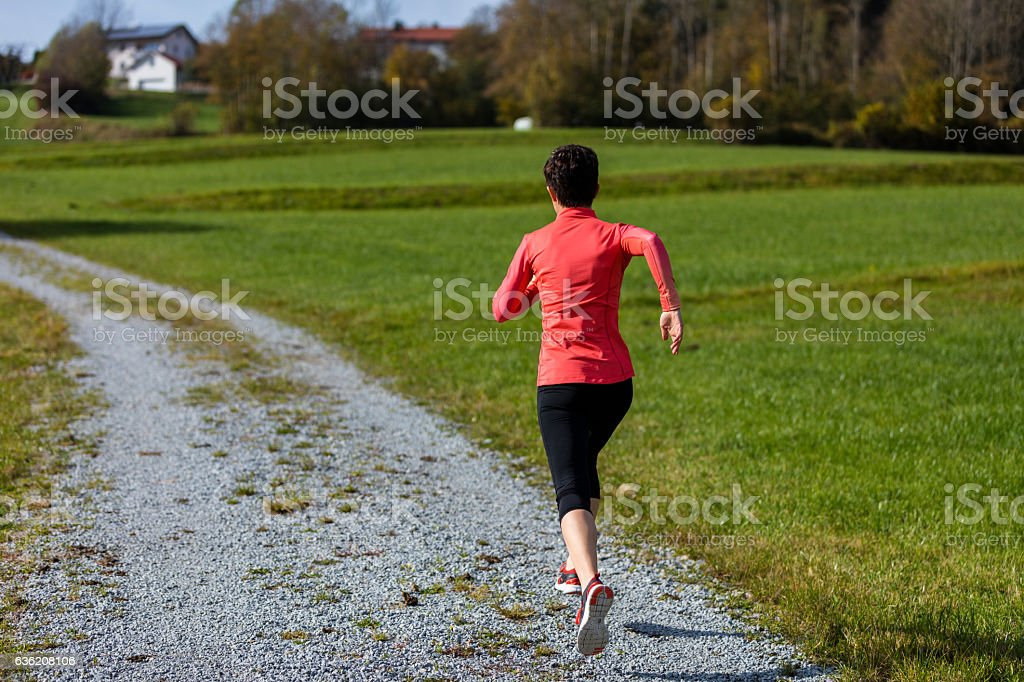 An athlete woman running outdoors, Bavarian National Forest Park stock photo
