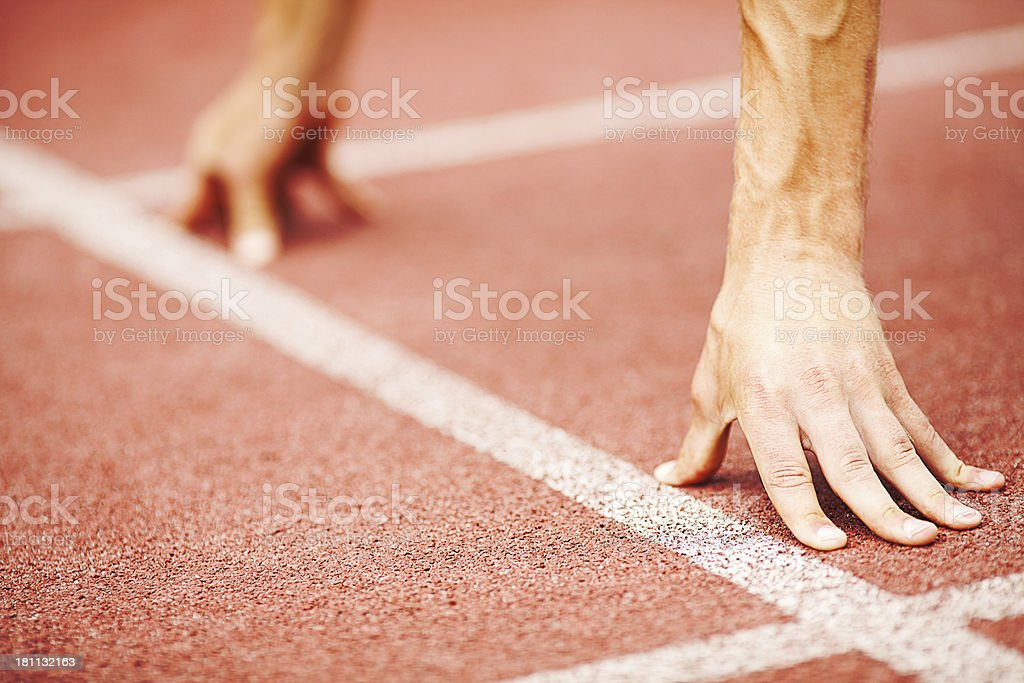An athletes hands on the get set position stock photo