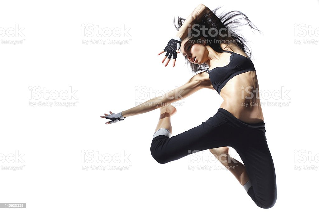 An athletic woman jumping up to strike a fierce pose royalty-free stock photo