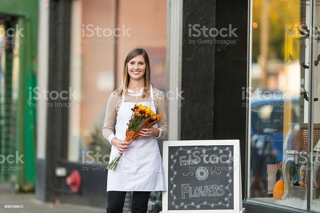 An attractive adult female business owner is holding stock photo