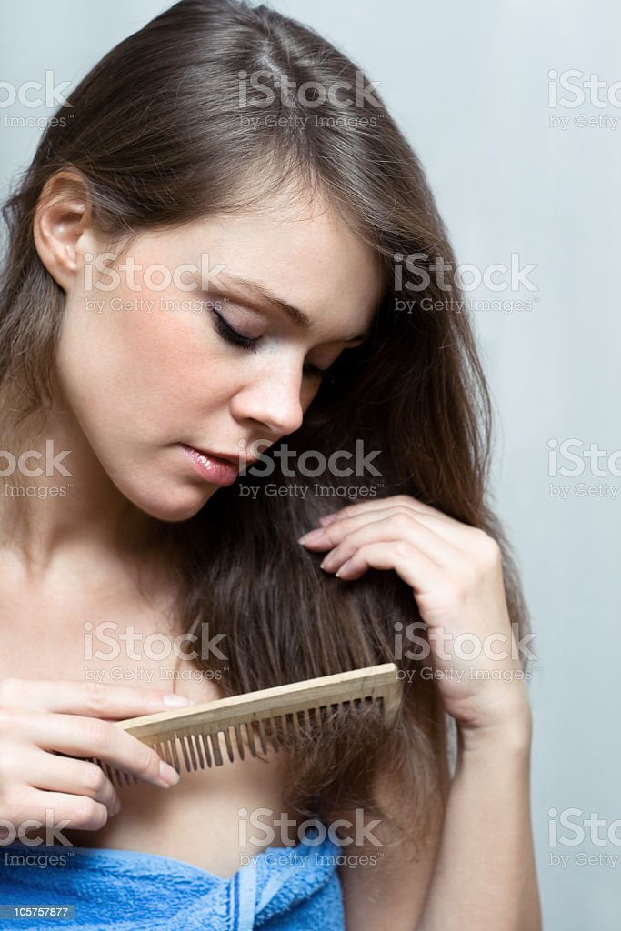 An attractive brunette female combing her medium length hair royalty-free stock photo