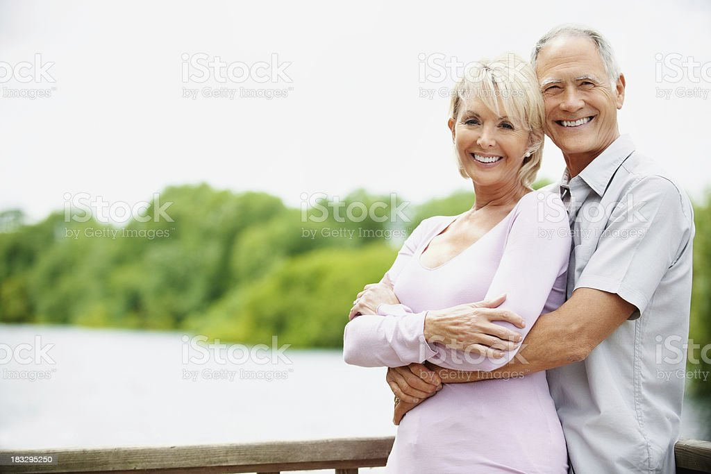 An attractive couple with man embracing a woman from back royalty-free stock photo