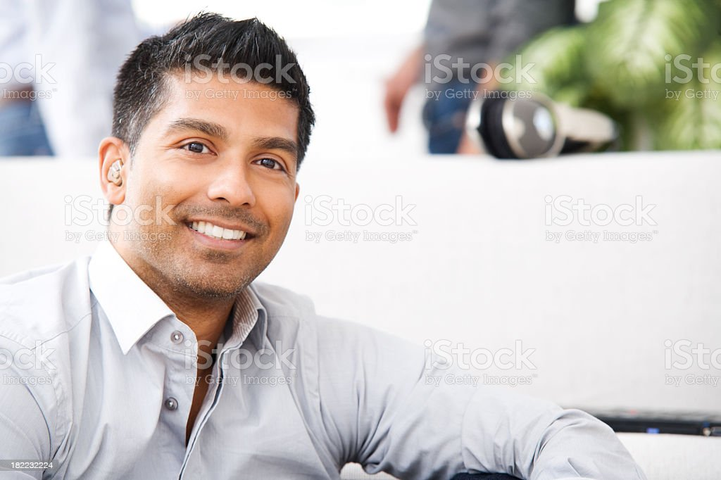 An attractive man is smiling while relaxing at home stock photo