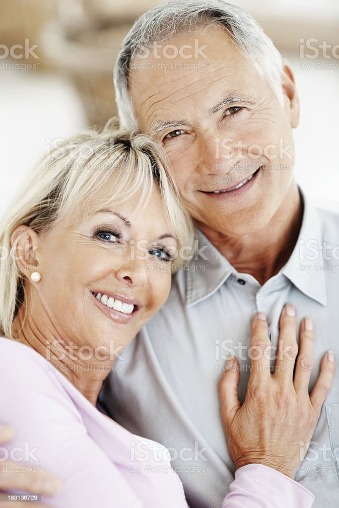 An attractive mature female resting on senior man's chest royalty-free stock photo