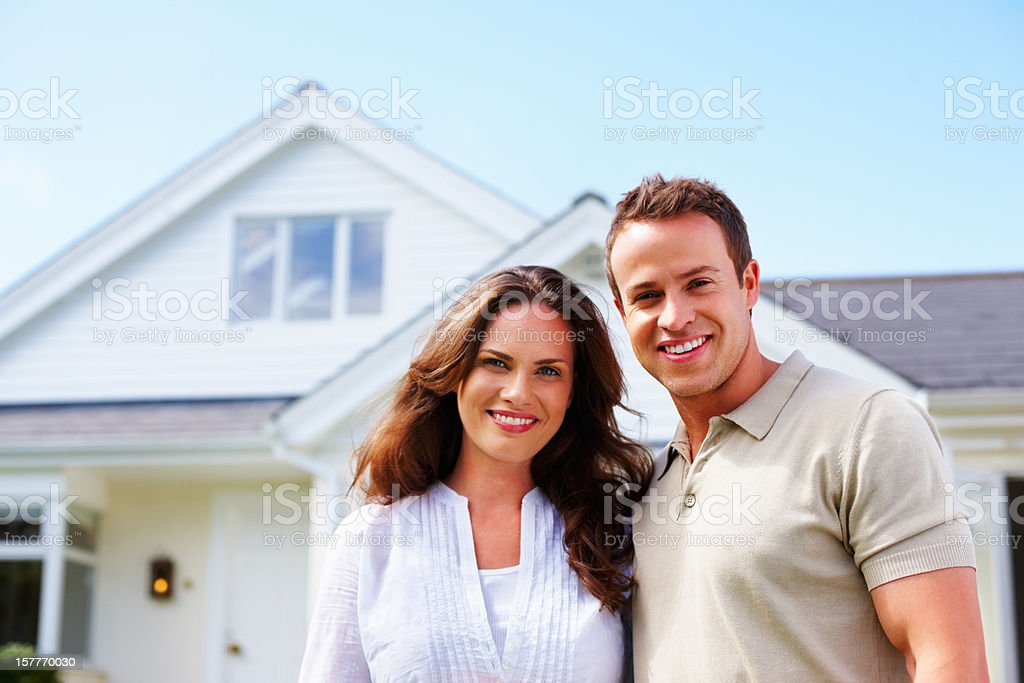 An attractive middle aged couple standing in front of house royalty-free stock photo
