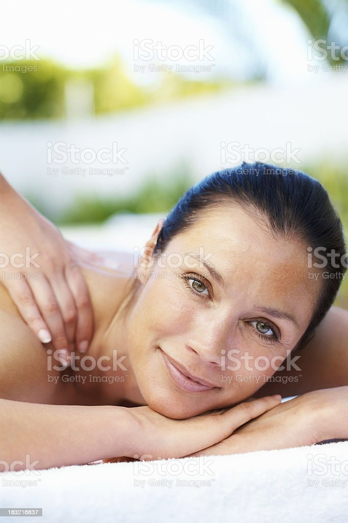 An attractive woman enjoying a shoulder massage royalty-free stock photo