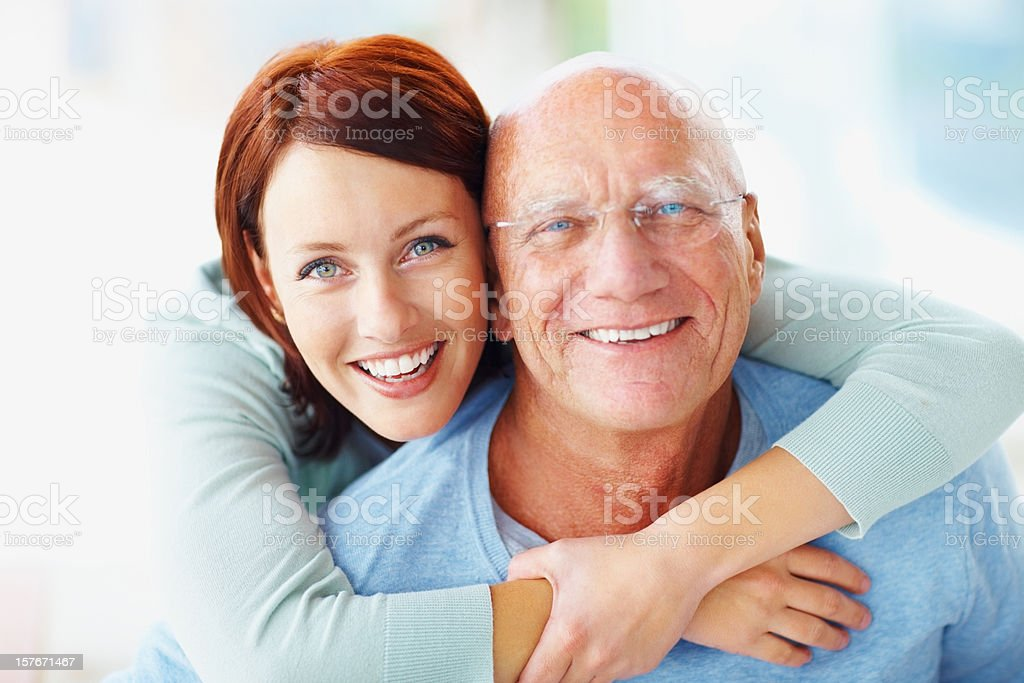 An attractive young woman embracing her grandfather from back royalty-free stock photo