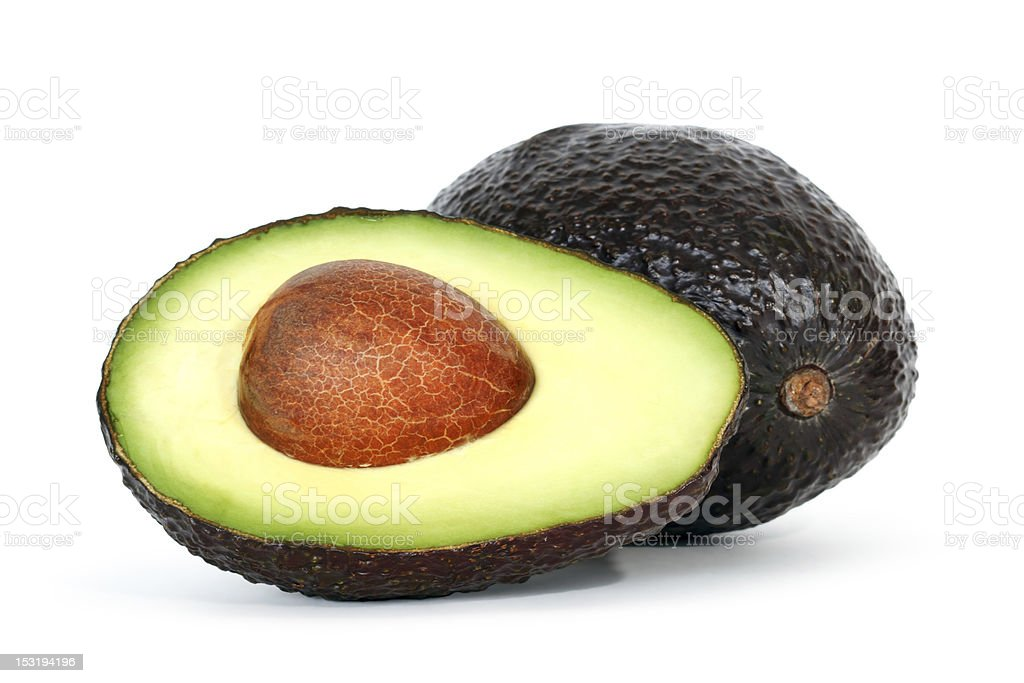 An avocado half with a brown seed and a whole avocado stock photo