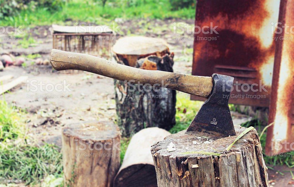 An axe on a stump in the garden stock photo