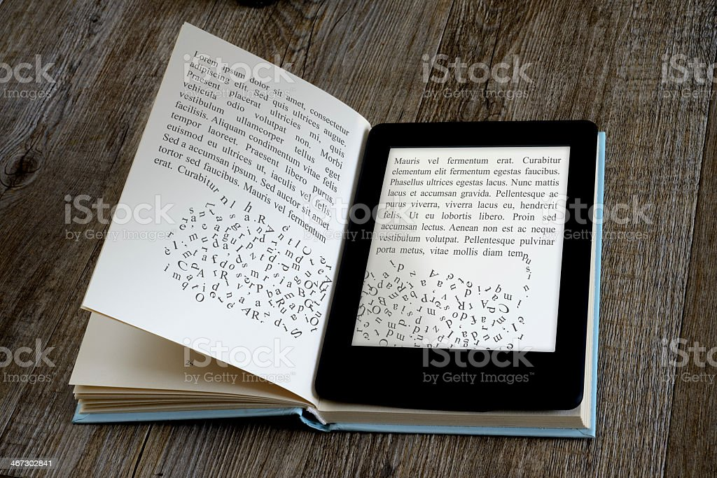 An ebook reader sitting on top of a paper book stock photo