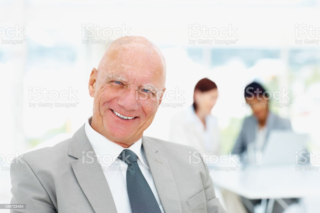 An elderly business man and his team working in background royalty-free stock photo