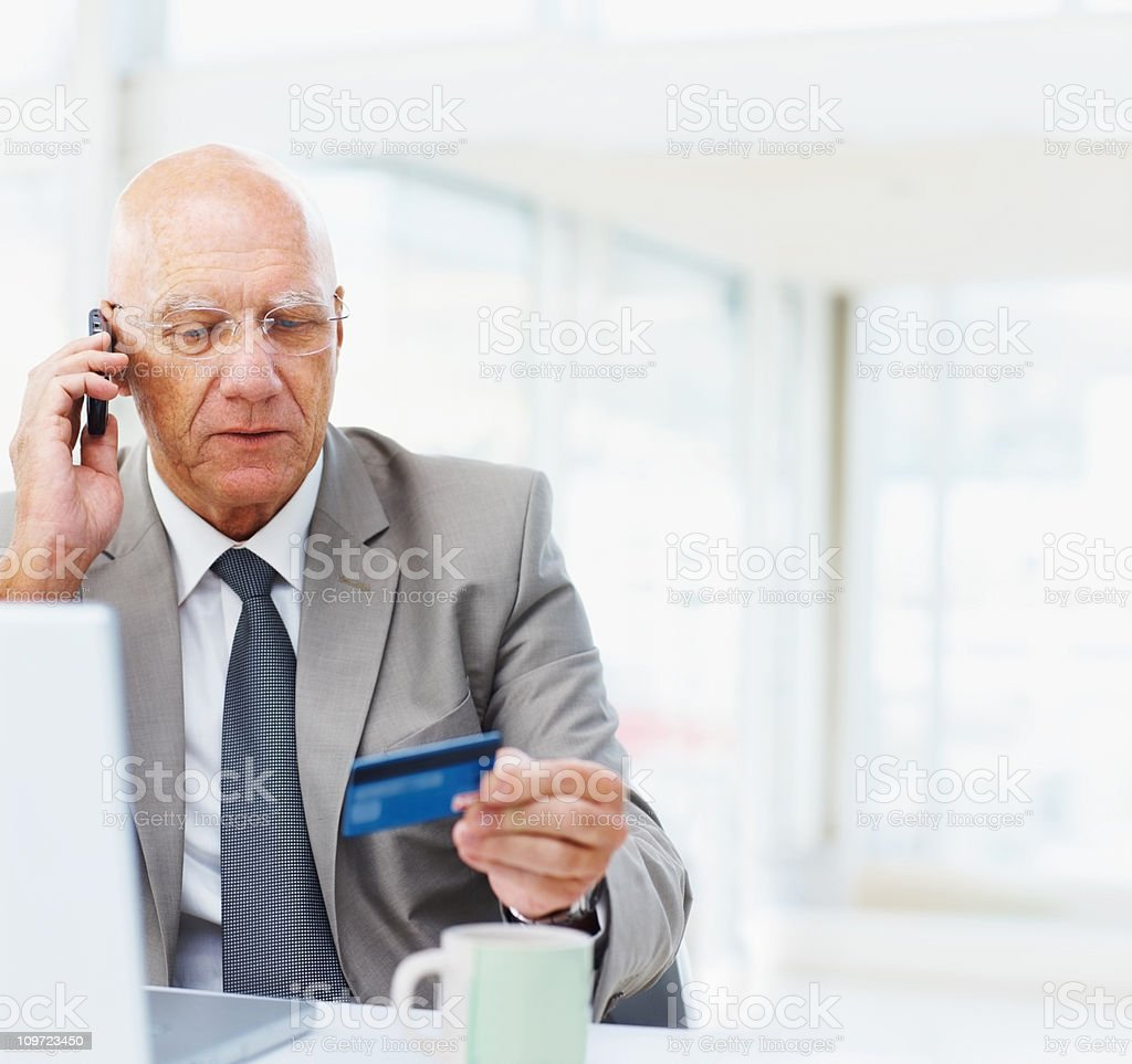 An elderly business man shopping online with a credit card royalty-free stock photo