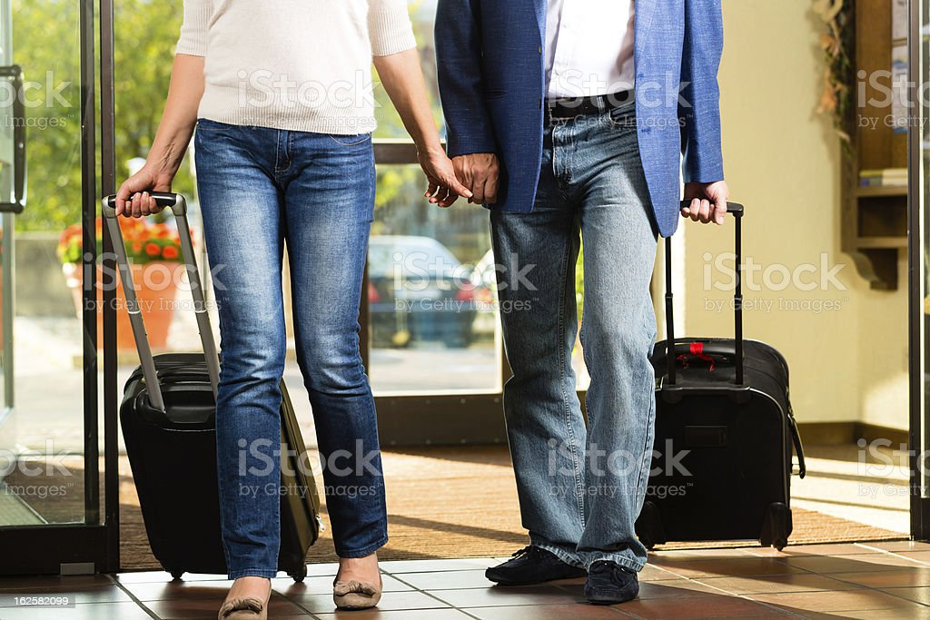 An elderly couple arriving at a hotel lobby stock photo