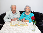 An Elderly Couple Praying and Reading Bible Together