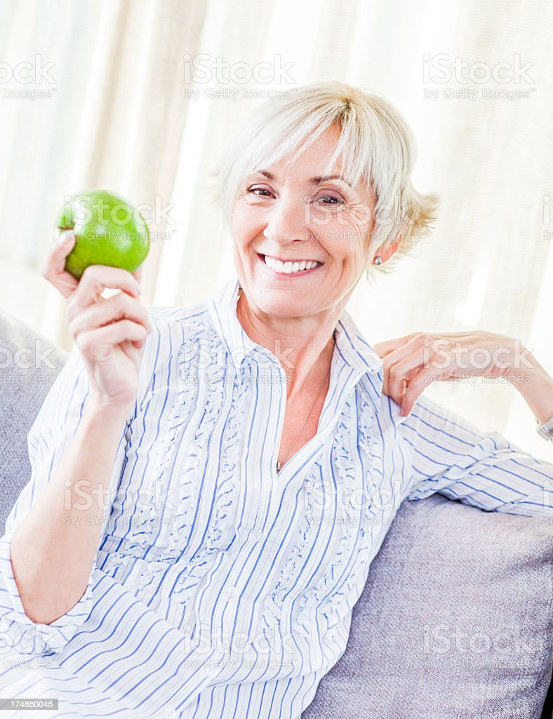 An elderly healthy woman grasping an apple royalty-free stock photo