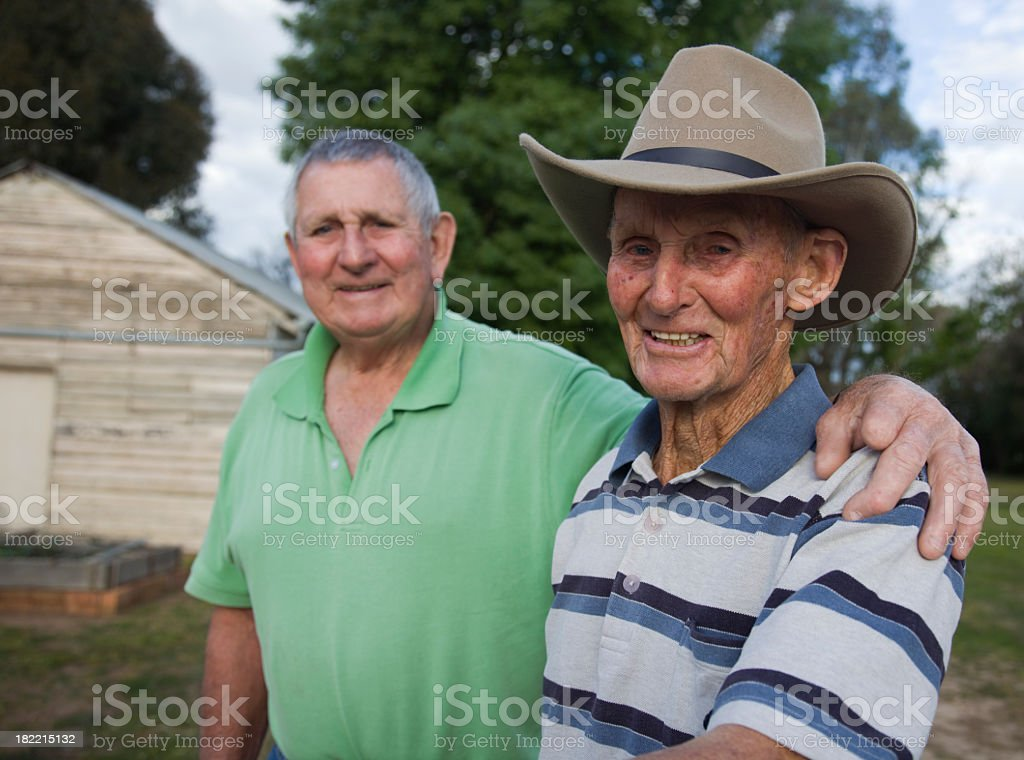 An elderly man and his younger brother standing outside stock photo
