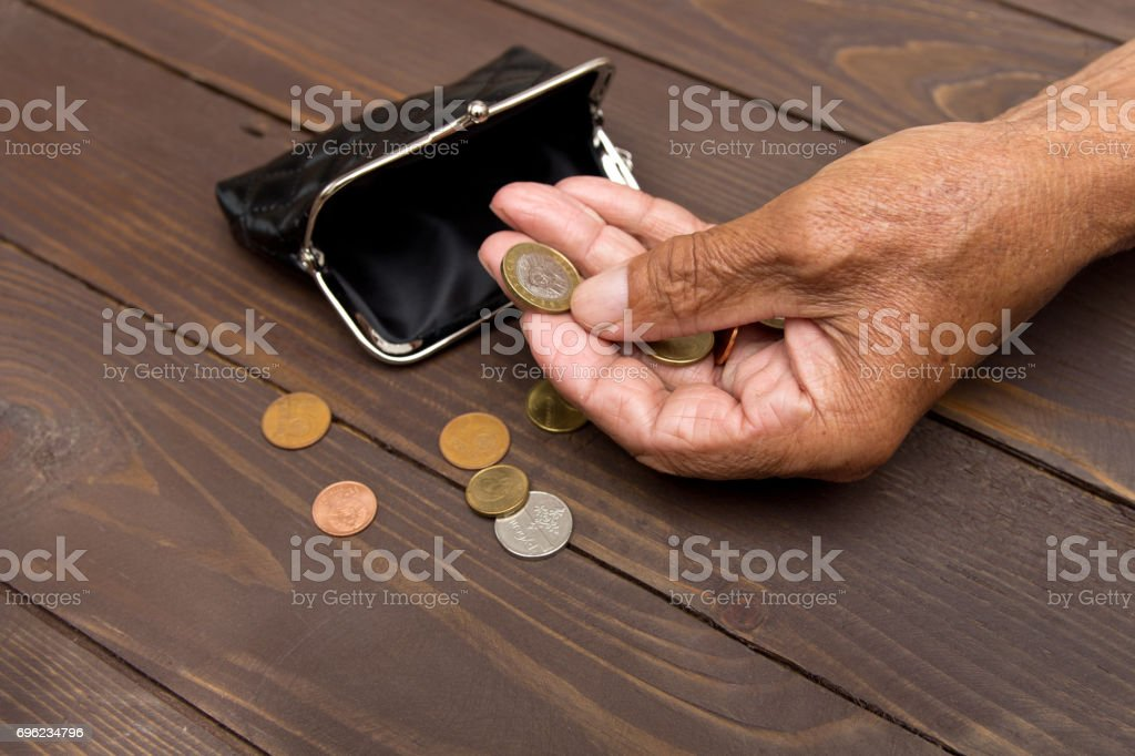 An elderly man holding an old coin purse and coins . The concept of poverty in retirement. stock photo