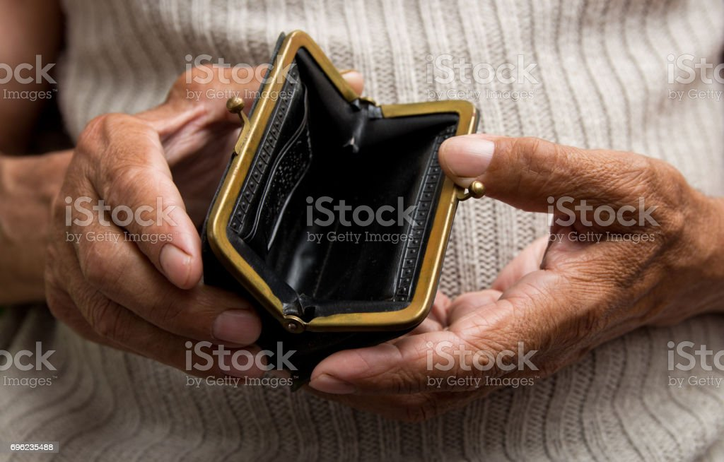 An elderly man holds an empty purse. The concept of poverty in retirement . stock photo