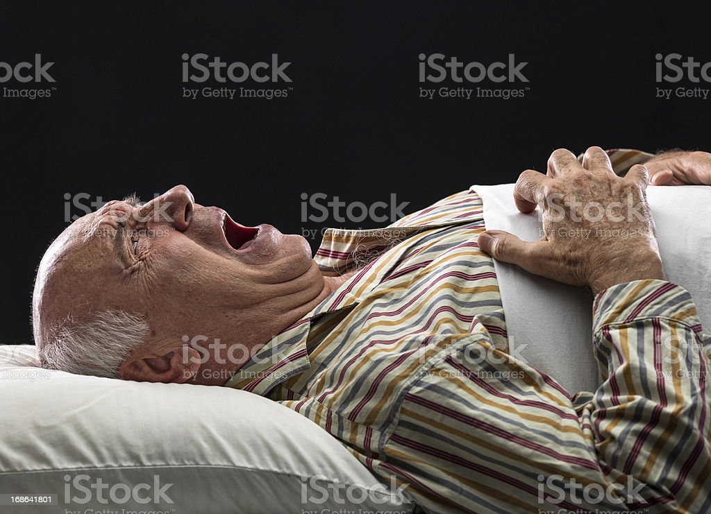 an elderly man laid in bed in severe agony stock photo