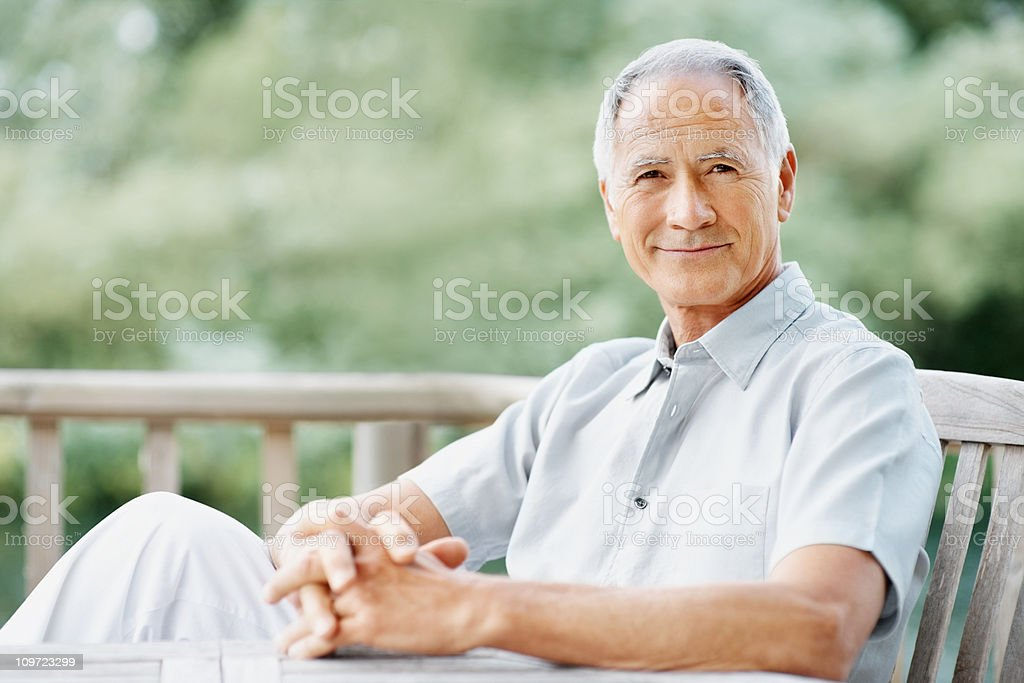 An elderly man sitting on a wooden bench royalty-free stock photo