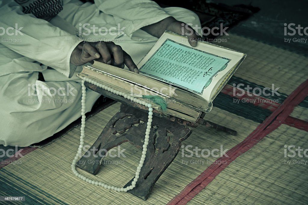 an elderly person reading concluding chapters of Quran on Friday stock photo