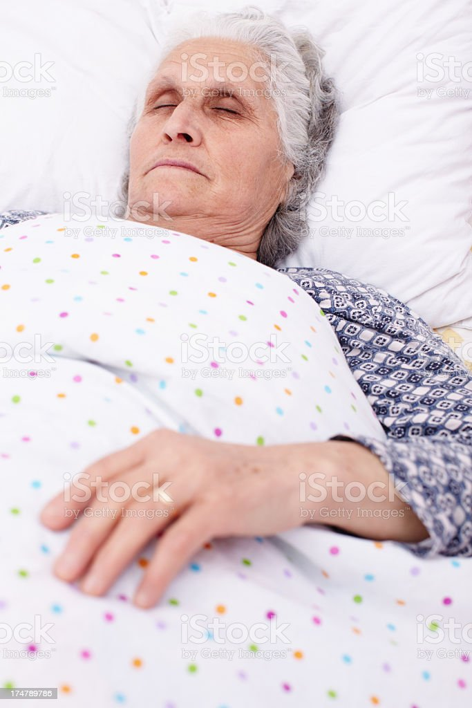 An elderly person sleeping in bed stock photo