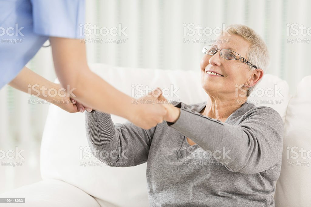 An elderly woman being helped up by a nurse royalty-free stock photo