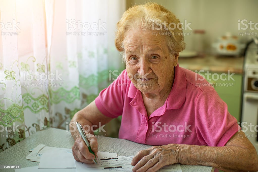 An elderly woman fills the bill on utility bills. stock photo