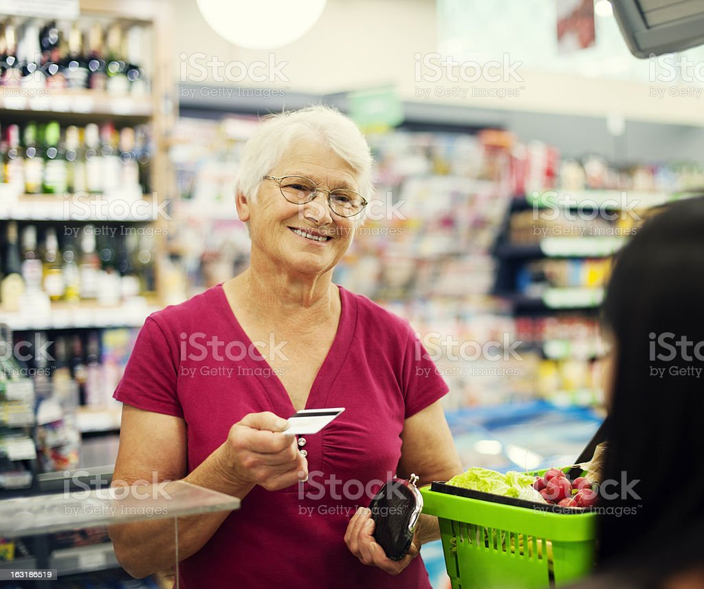 An elderly woman paying with a credit card stock photo