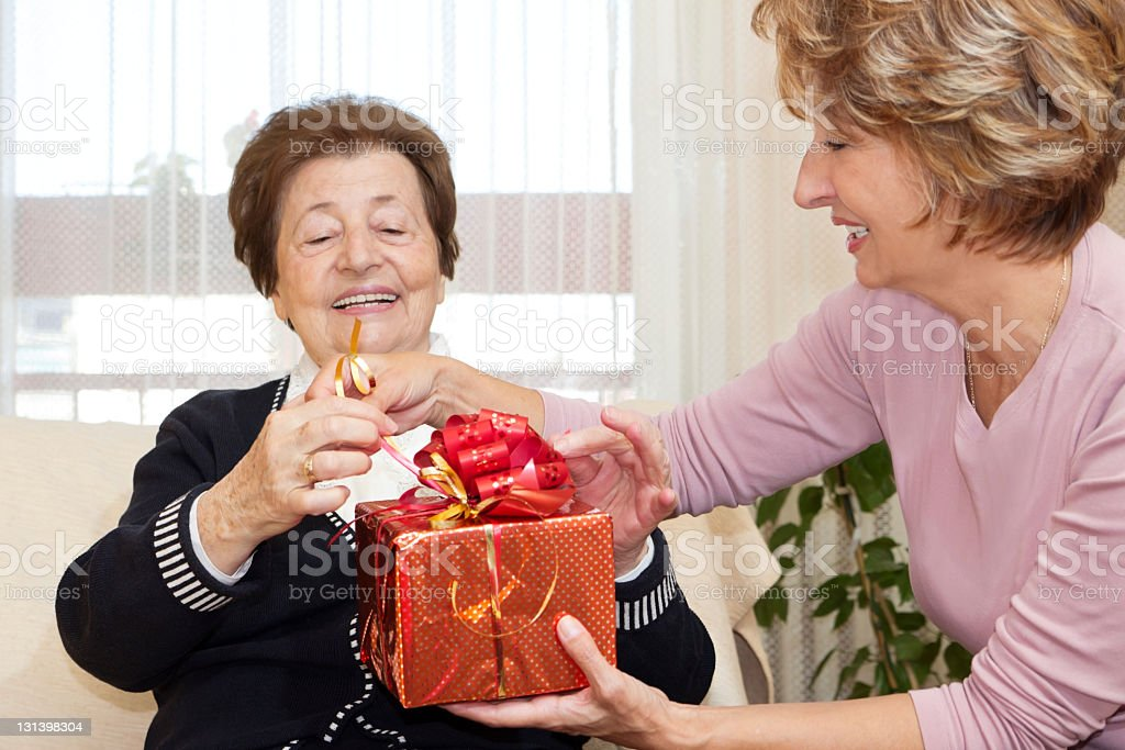 An elderly woman receiving a gift royalty-free stock photo