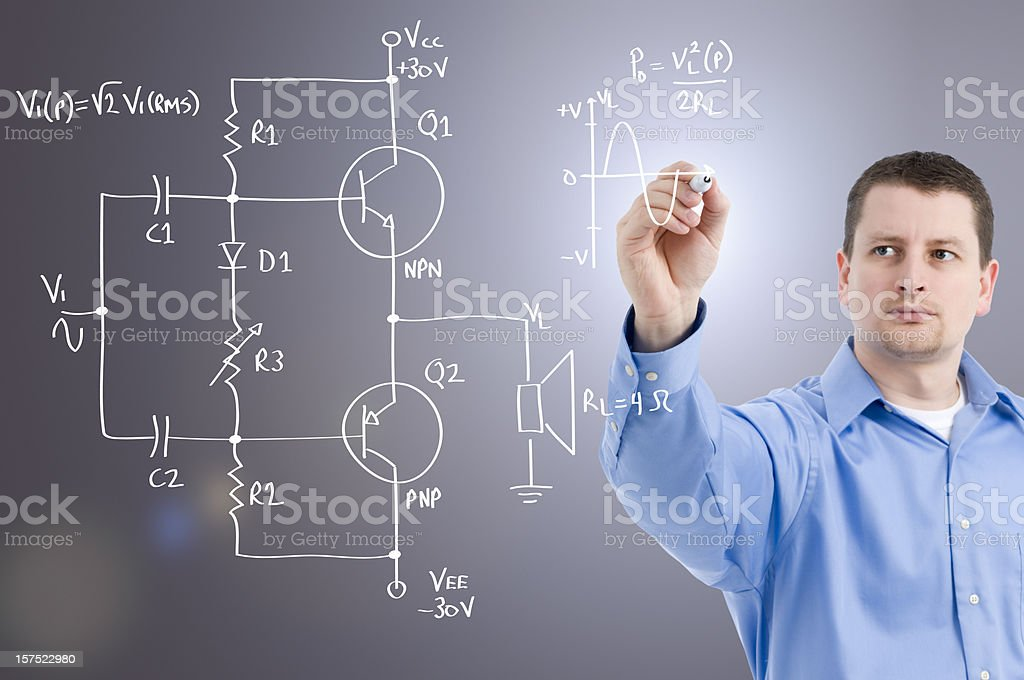 An electronics engineer drawing a circuit on glass wall stock photo