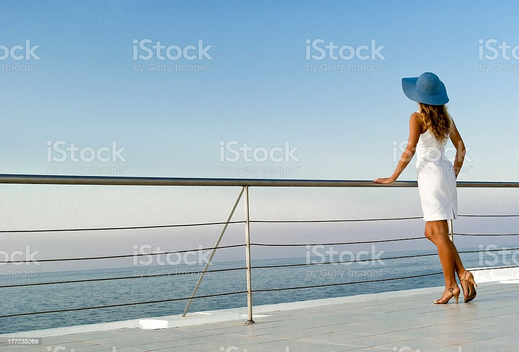 An elegant woman standing against a railing looking at sea stock photo