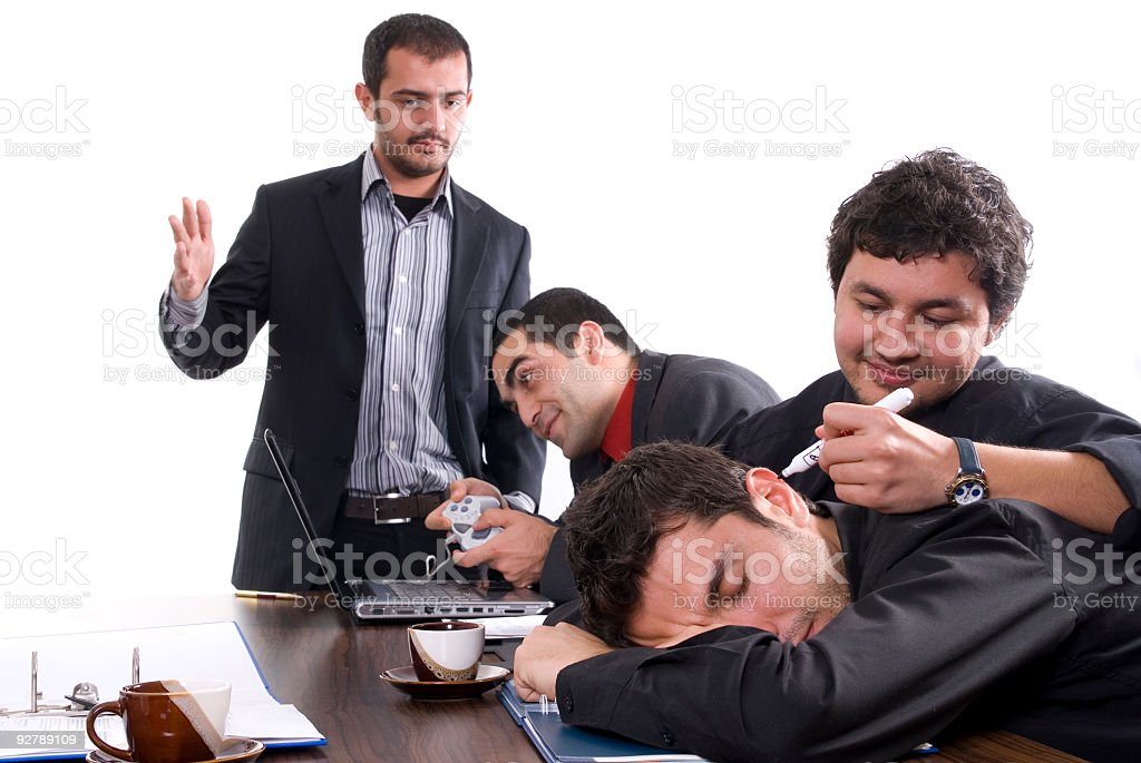 An employee playing a video game while the other is sleeping royalty-free stock photo