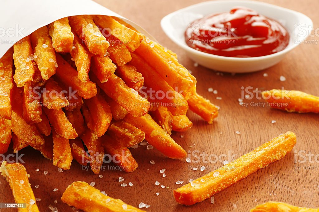 An emptied out cup of sweet potato fries and tomato ketchup stock photo