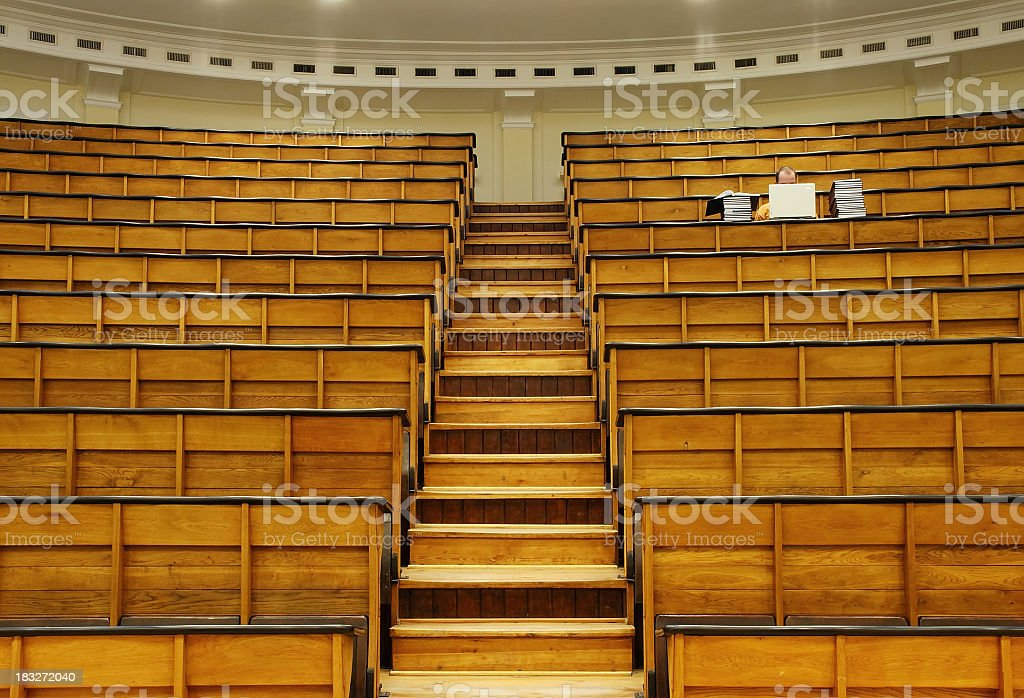 An empty auditorium with one single man studying royalty-free stock photo