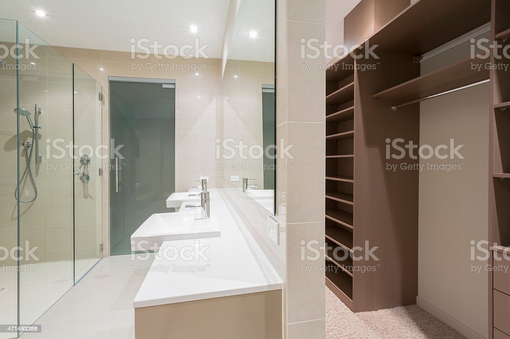 An empty bathroom with double sinks and a walk-in closet stock photo