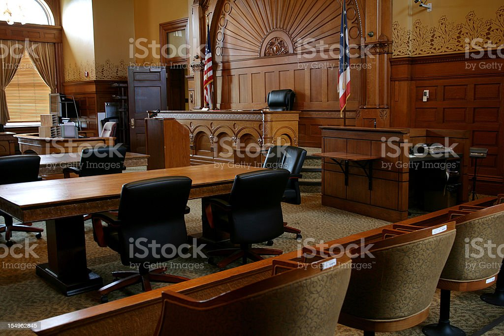 An empty, brown-paneled courtroom with flags stock photo