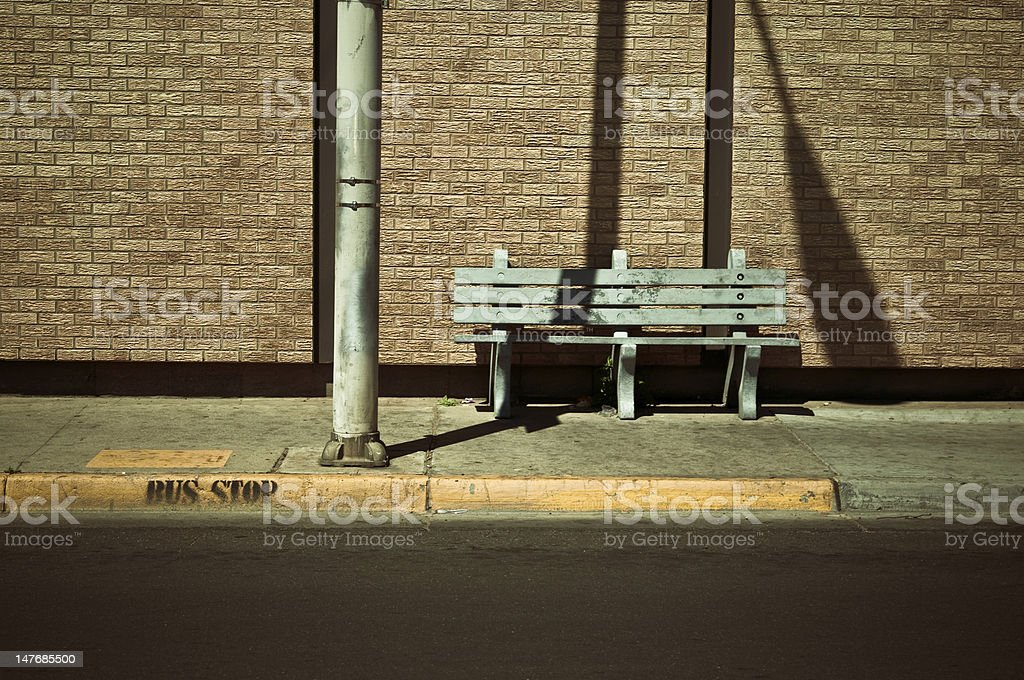 An empty bus stop in the shadows stock photo