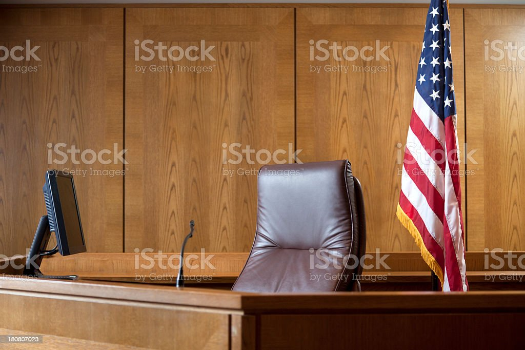 An empty courtroom bench with U S flag stock photo